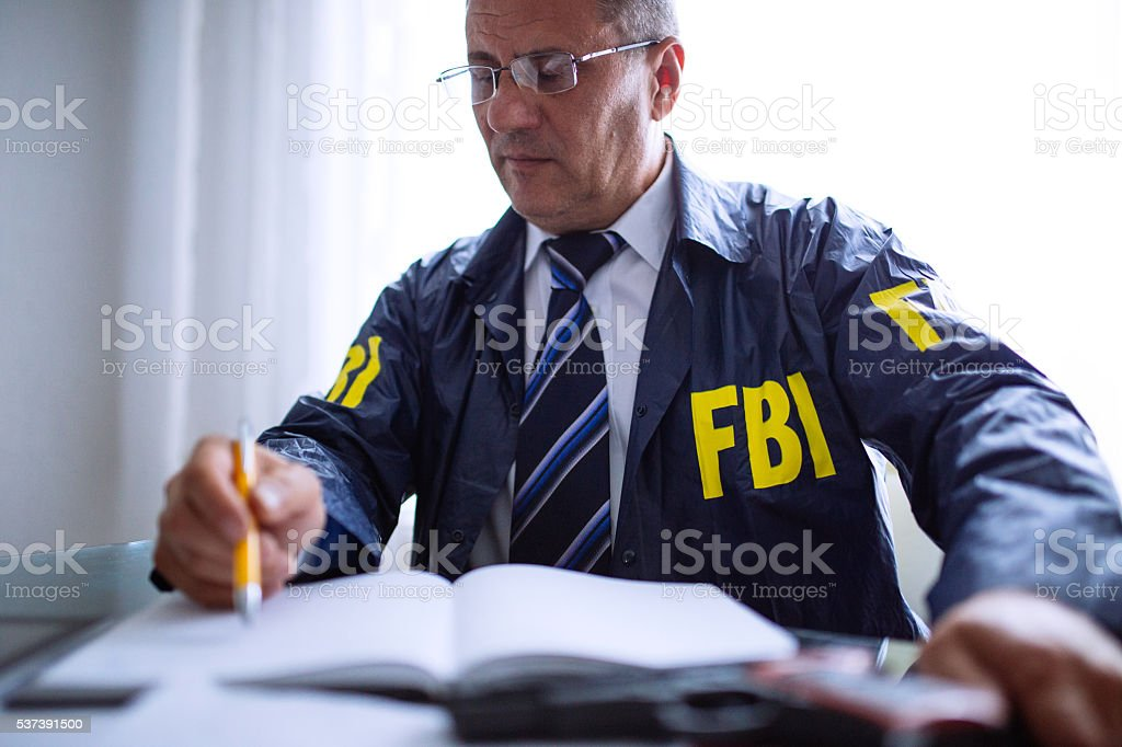 FBI agent writing at his office stock photo