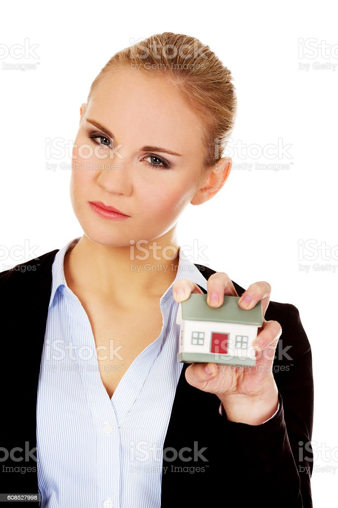 Aggresive business woman crushing small house stock photo
