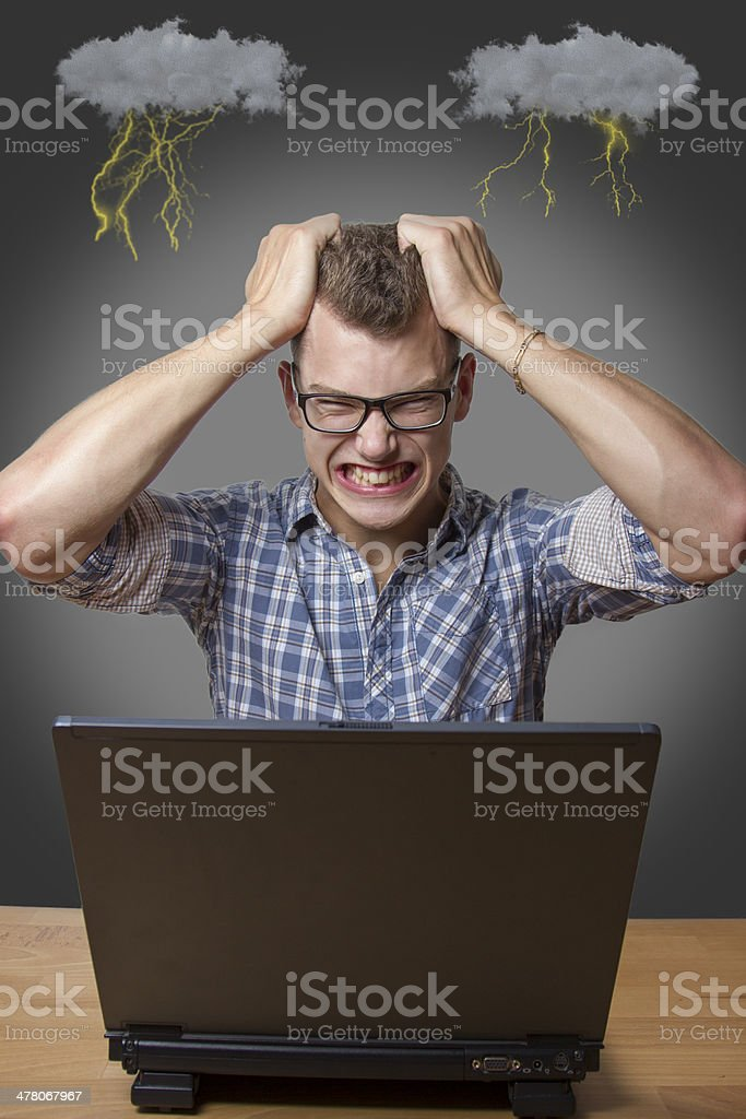 Aggressive boy sitting at the Computer stock photo