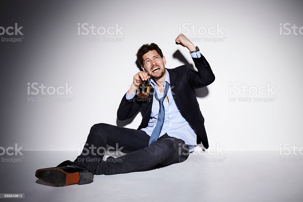 Aggressive drunk businessman shaking fist in studio stock photo