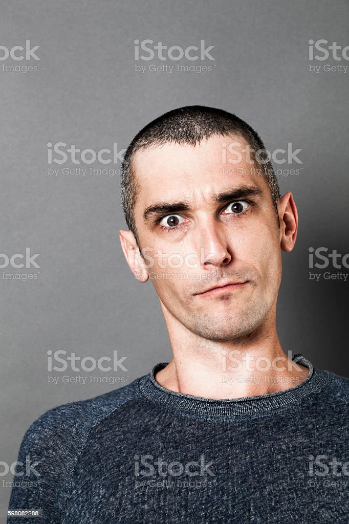 aggressive man looking skeptical, scary and surprised, expressing suspicion stock photo