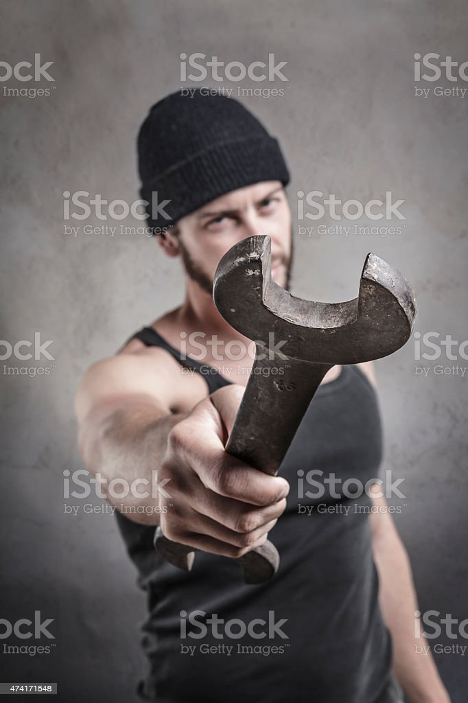 Aggressive man using a wrench as a weapon stock photo