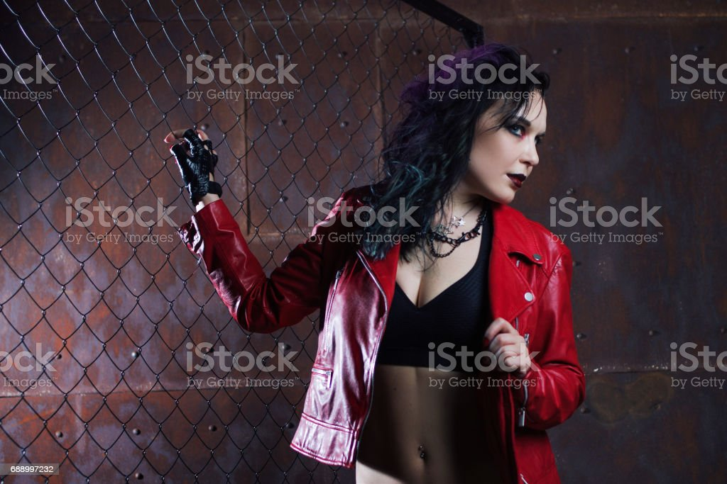 Aggressive punk woman, in red leather jacket stock photo