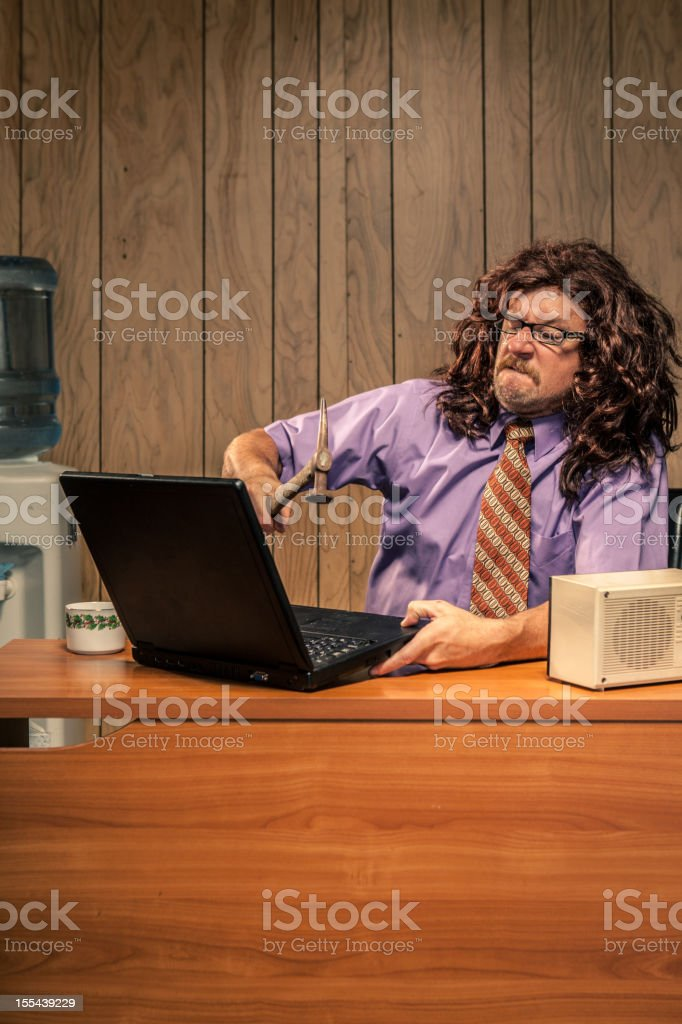 Aggressive Retro Office Worker Smashing his Computer with Hammer royalty-free stock photo