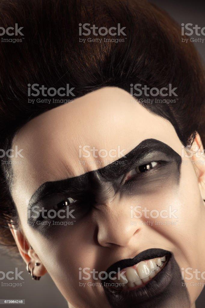 aggressive woman face with creative dark make-up stock photo