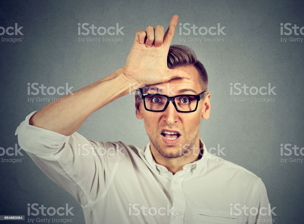 Aggressive young man in glasses showing loser sign gesture on forehead stock photo