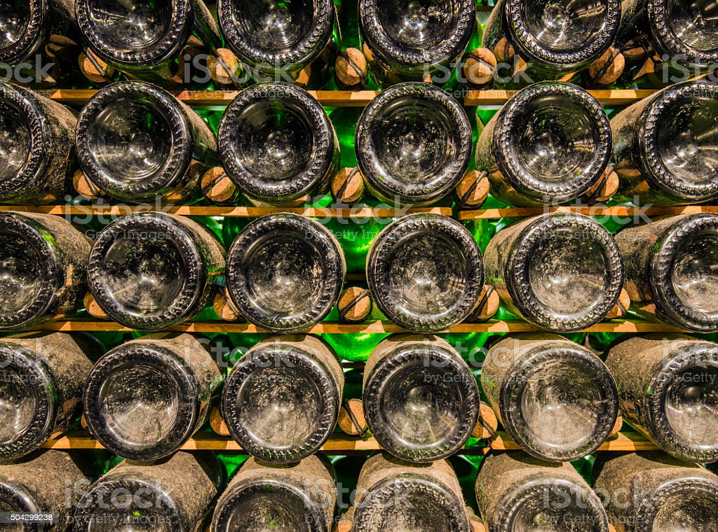 Aging champagne bottles in cellar stock photo