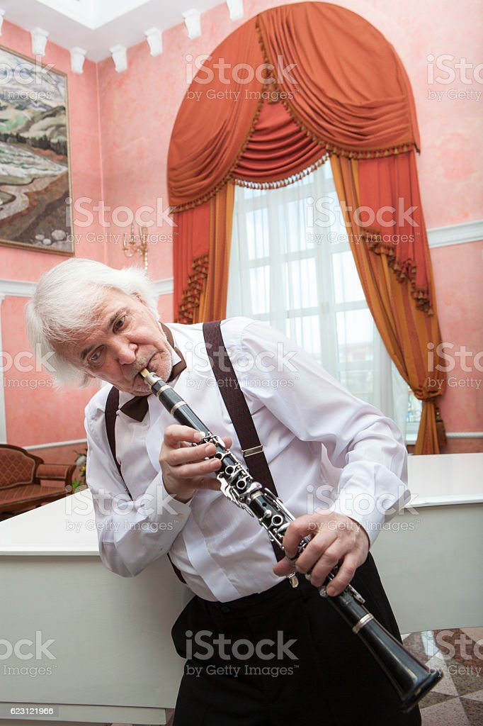 aging musician plays the clarinet stock photo