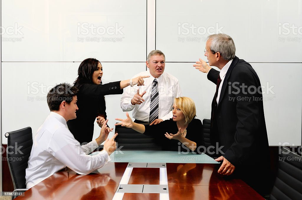 Agitated business people at a meeting pointing at each other royalty-free stock photo