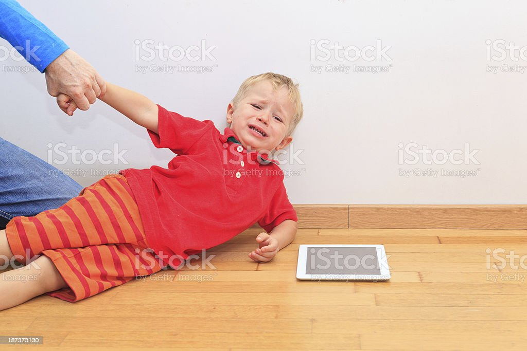 Agitated child being pulled away by parent from iPad stock photo