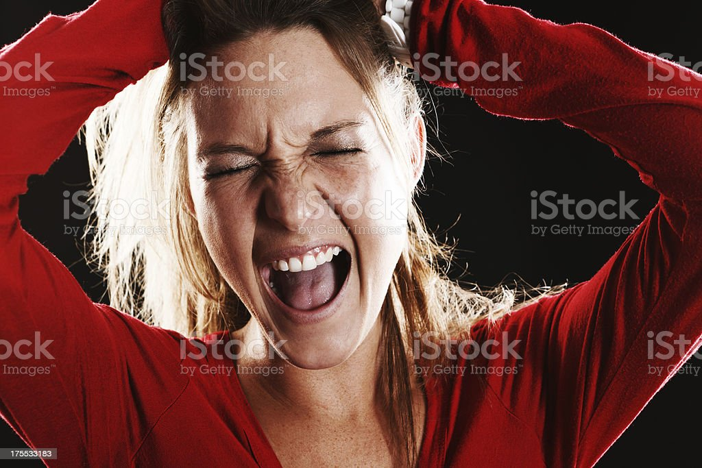 Agony or ecstasy: Young blonde grimaces, hands to head stock photo