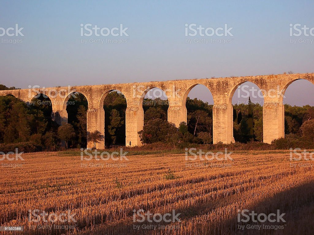 Agricultural field under abandoned aqueduct at sunset stock photo