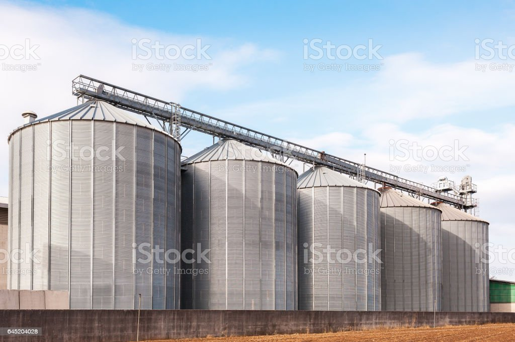 Agricultural silos on blue sky. stock photo
