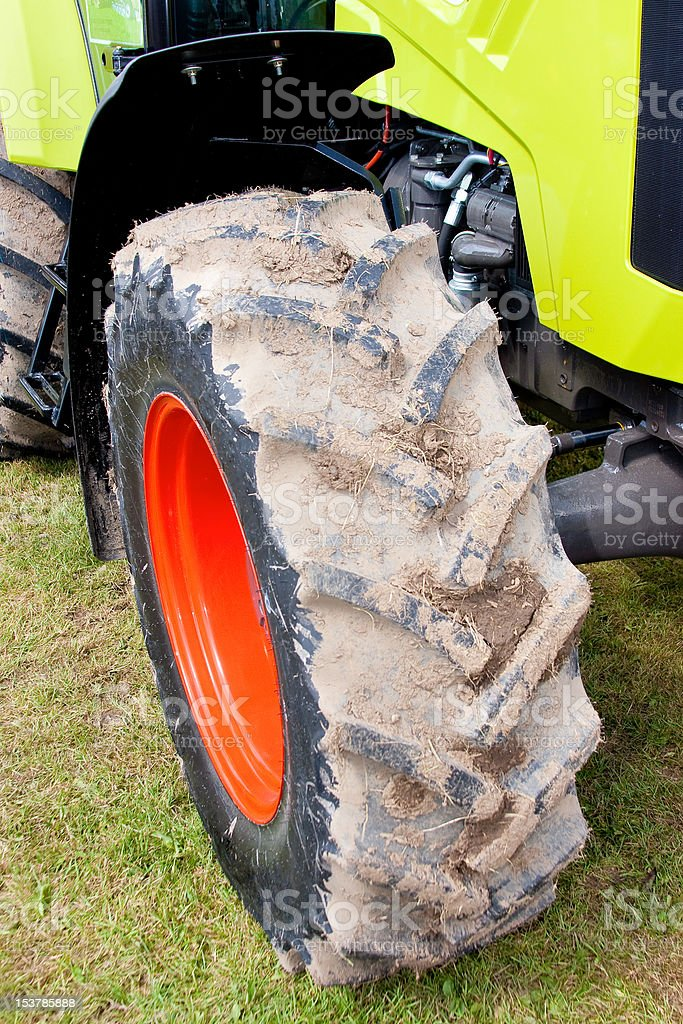 Agricultural Tractor Detail of Red Wheel with Vibrant Green Body royalty-free stock photo