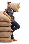 Agricultural worker with burlap sack leaning on stack of burlap