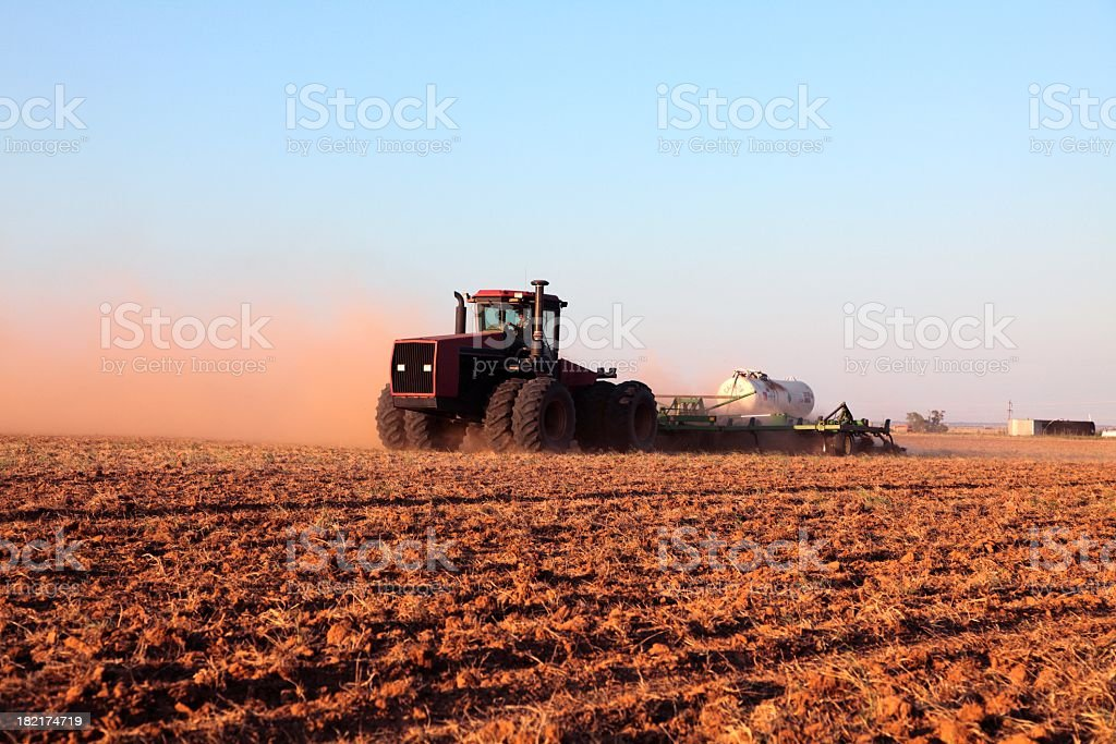 Agriculture: Farmer driving tractor with Fertilizer Tank in plowed field royalty-free stock photo