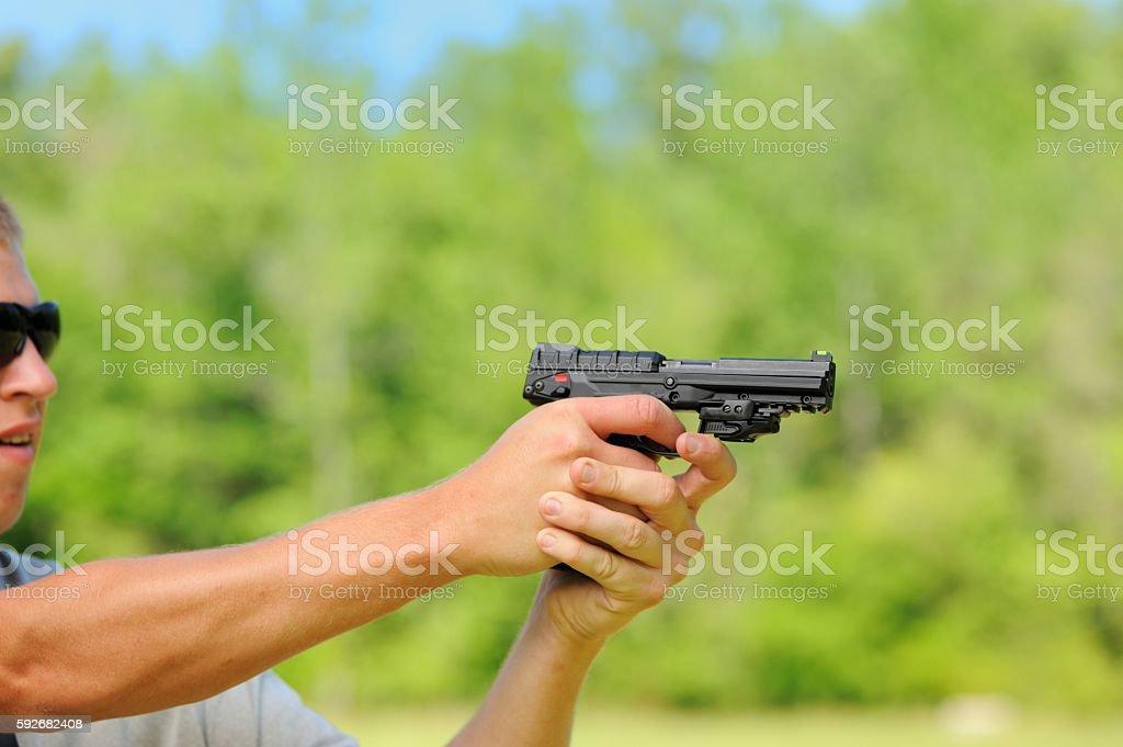 Aiming a semi automatic pistol on outdoor range stock photo