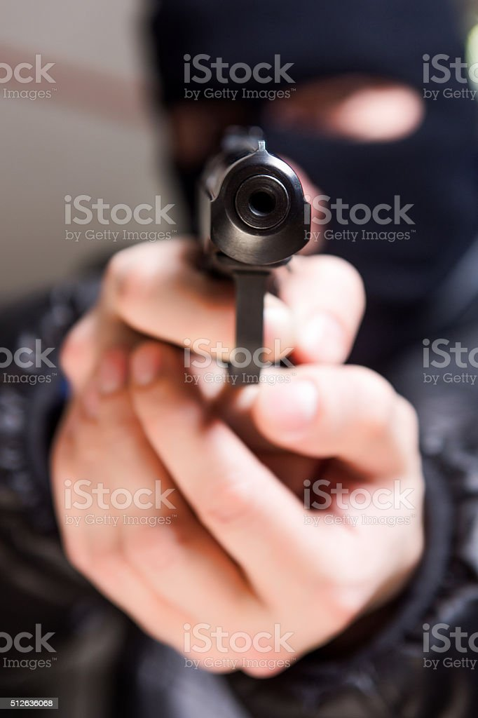 Aiming murderer with a gun stock photo