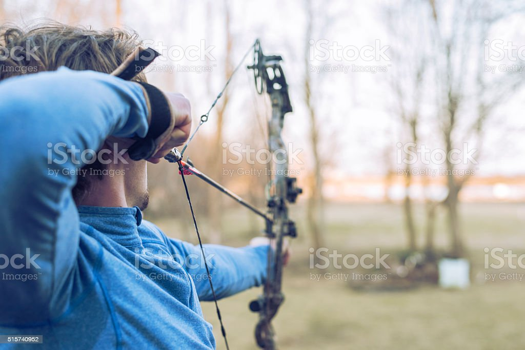 aiming with bow and arrow towards target in woods stock photo