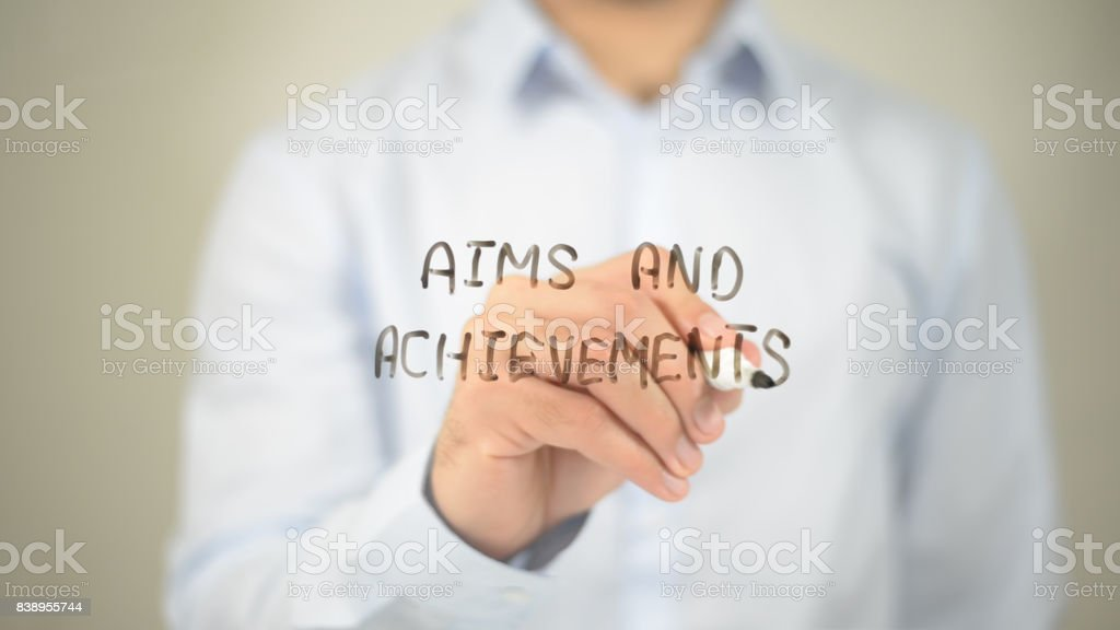Aims and Achievements, man writing on transparent screen stock photo