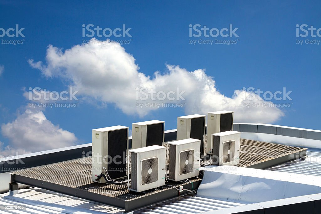 air condition outdoor unit, on the roof with blue sky stock photo