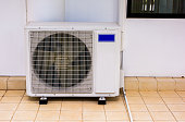 Air conditioner compressor installed on tiles floor outside building