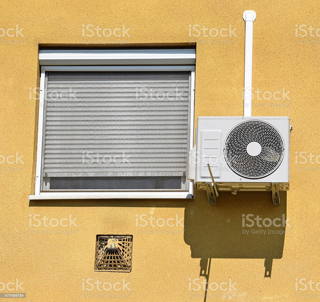 Air conditioner on the wall next to a window stock photo