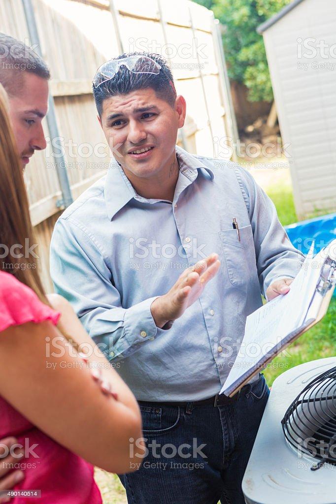 Air conditioner repairman giving homeowners estimated cost of repairs stock photo