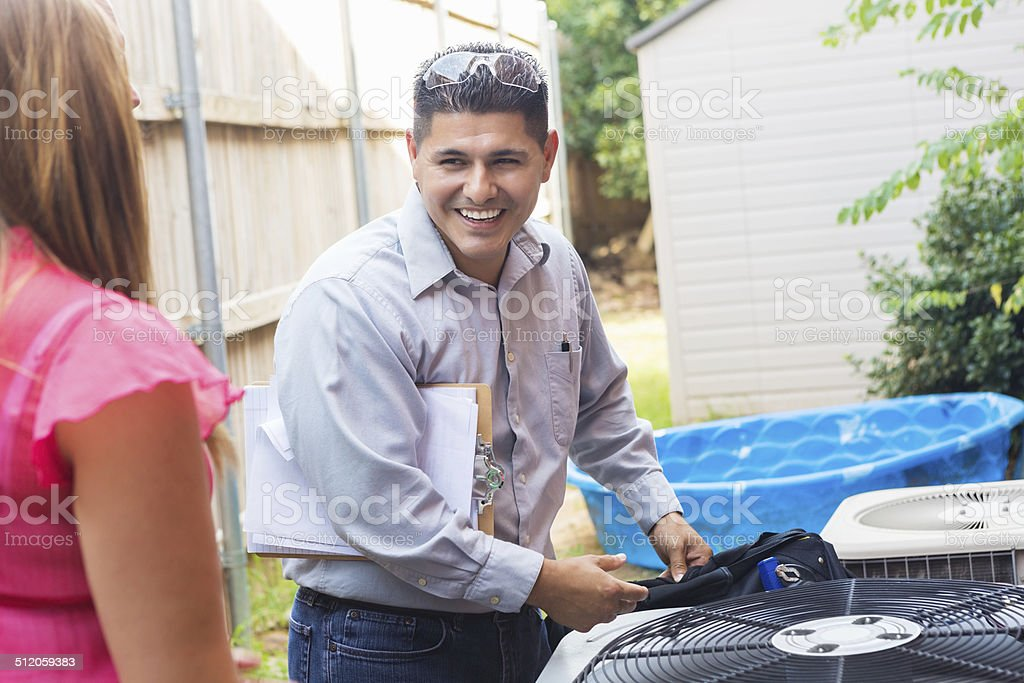 Air conditioner repairman talking to homeowner while inspecting unit stock photo