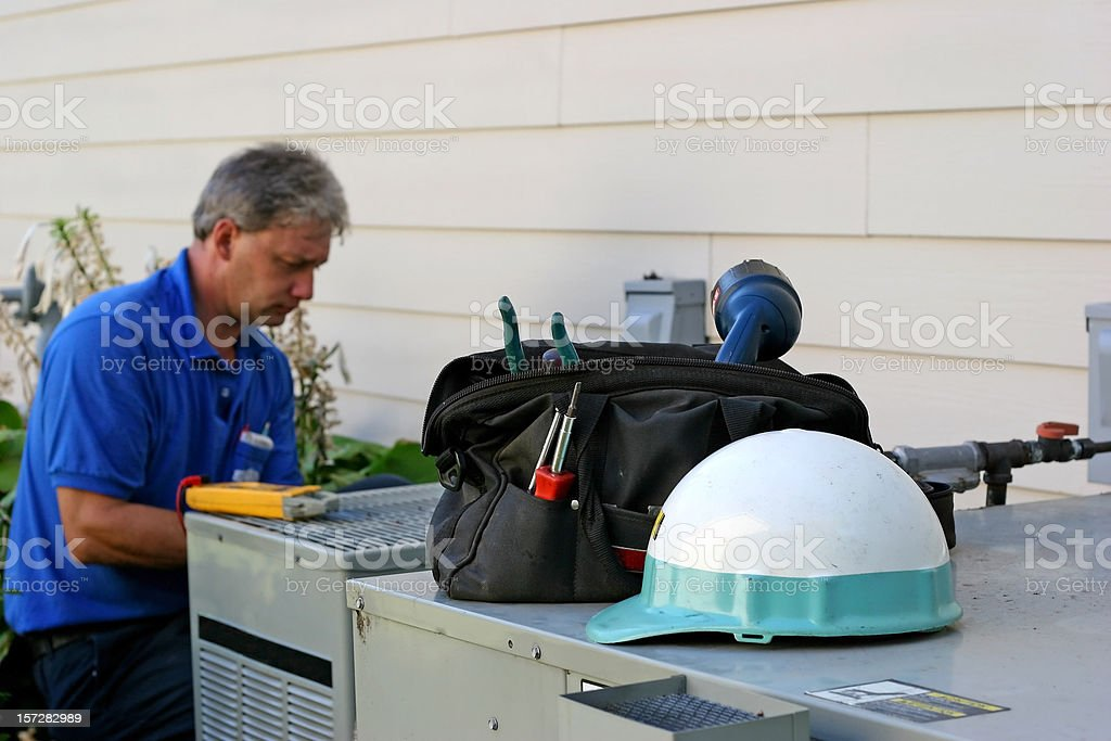 Air conditioner repairman working on an outdoor unit stock photo