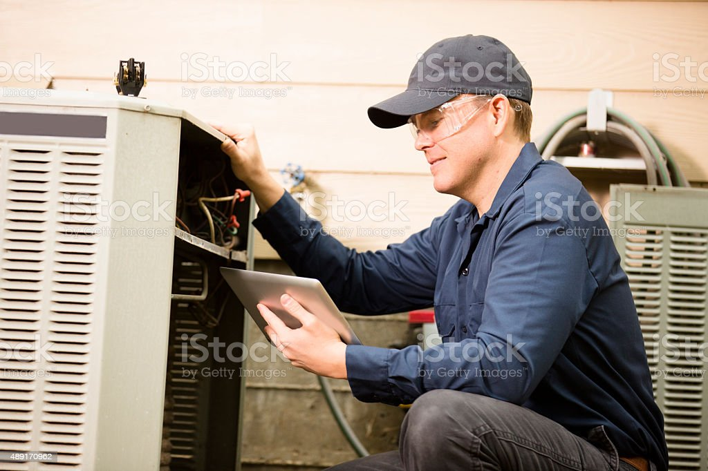 Air conditioner repairman works on home unit. Blue collar worker. stock photo
