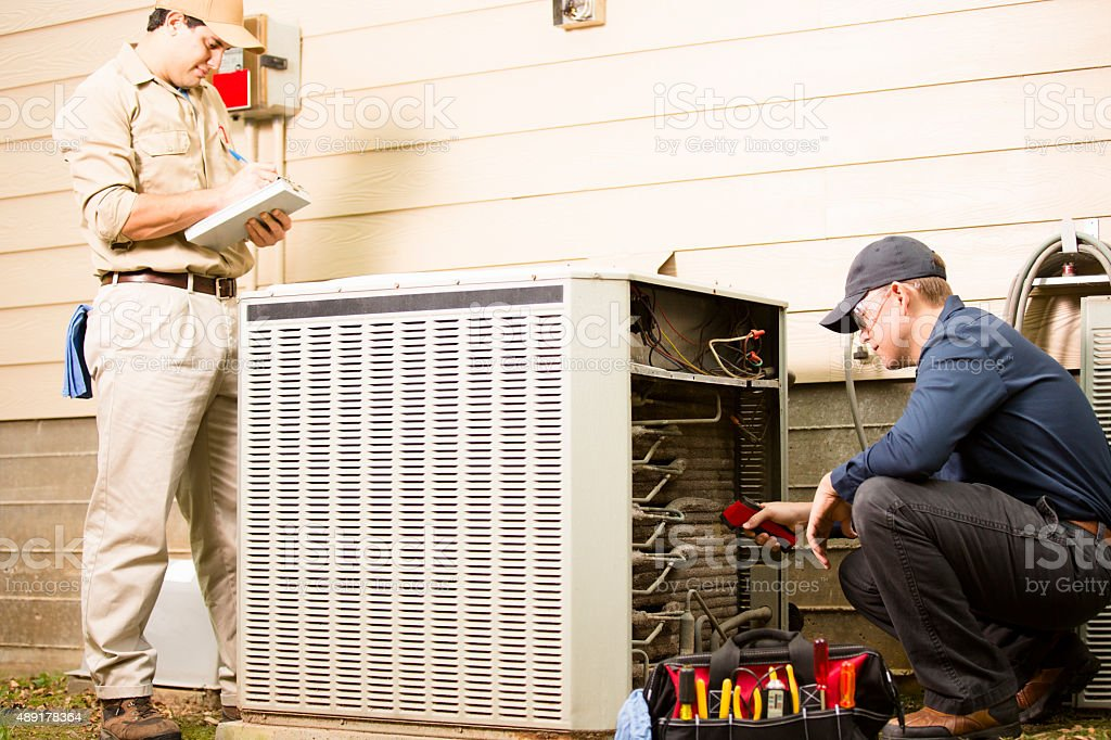 Air conditioner repairmen work on home unit. Blue collar workers. stock photo