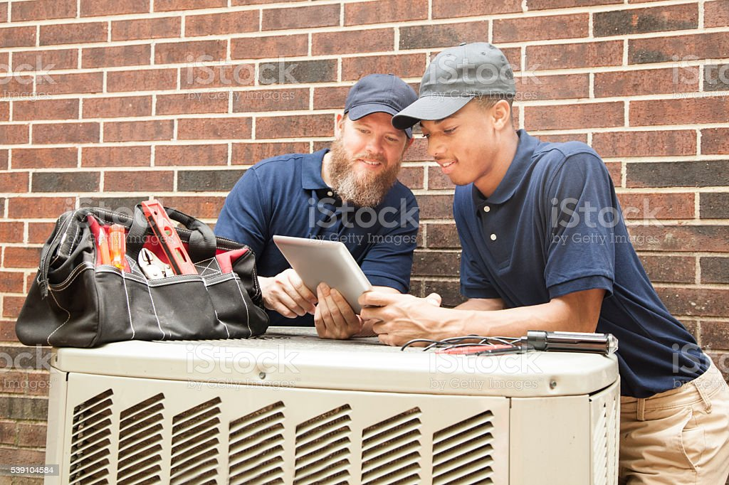 Air conditioner repairmen work on home unit.  Digital tablet. stock photo