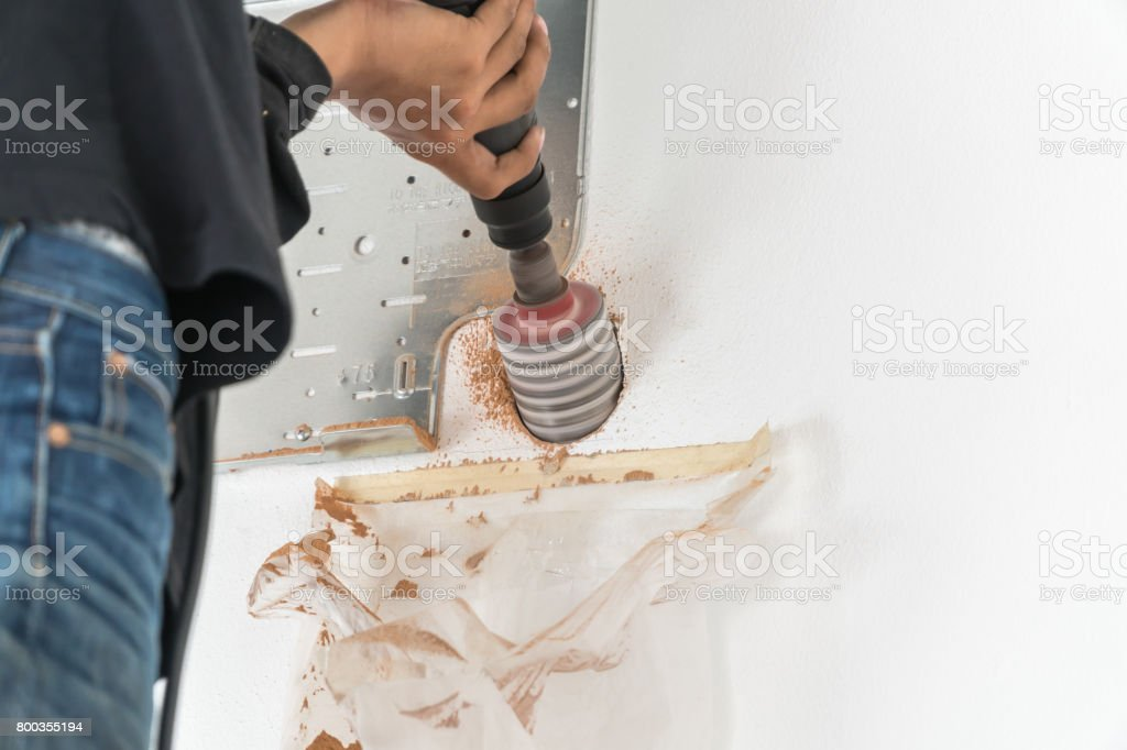 Air Conditioning Technician drills the wall stock photo