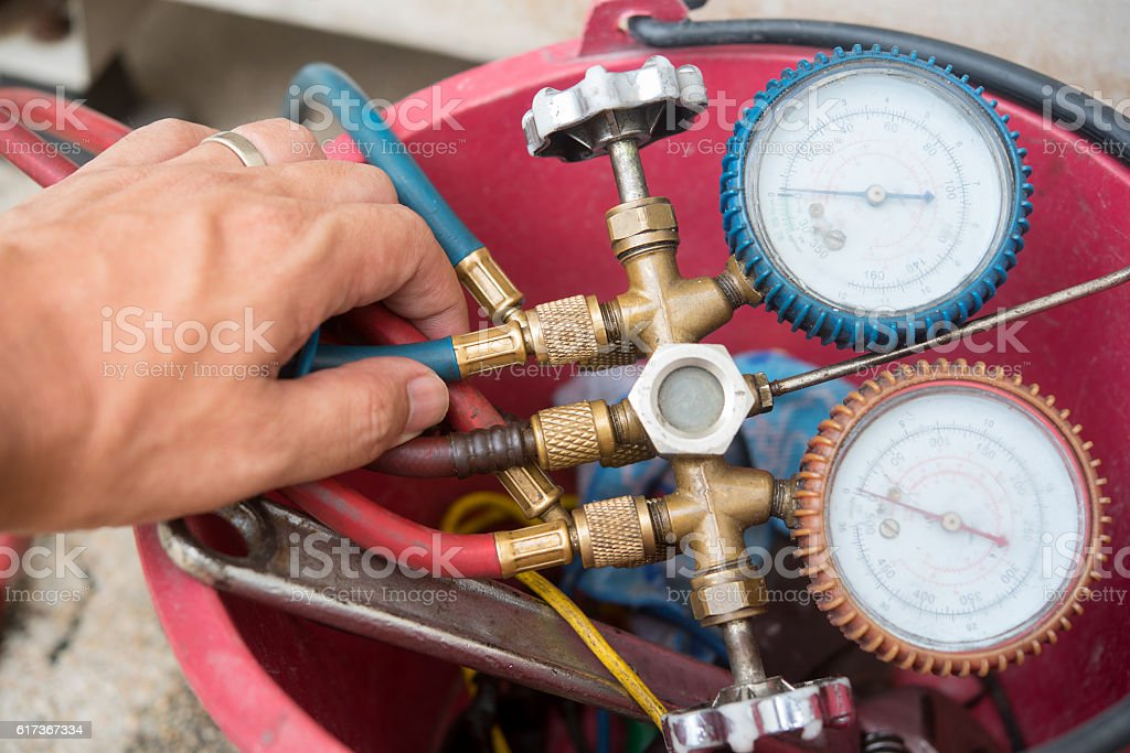 Air Conditioning Technician install new air conditioner. stock photo