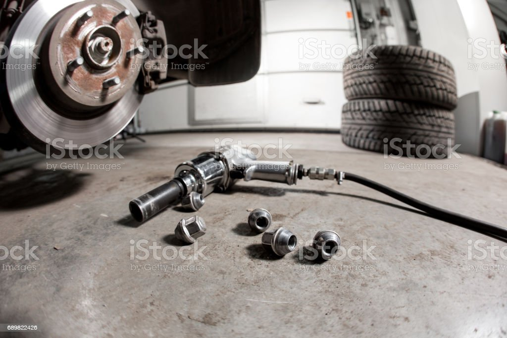 air gun to tighten a tire bolts on a suspended car at an auto shop stock photo