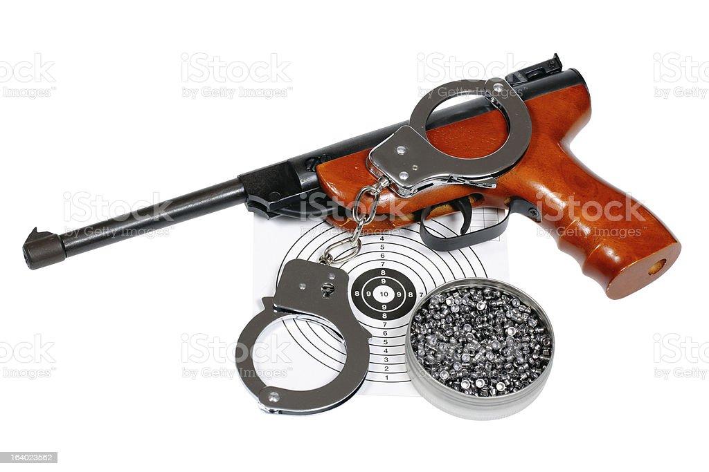 Air gun with gun-shield, pellets in box and handcuffs royalty-free stock photo