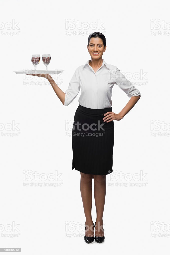 Air hostess carrying a tray of wine glasses stock photo