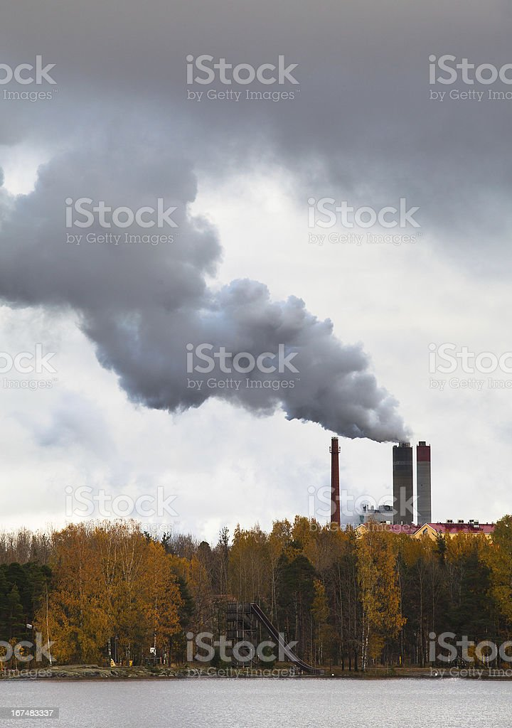 Air pollution by smoke coming out of three factory chimneys. royalty-free stock photo