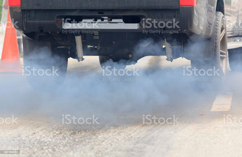 Air pollution from vehicle exhaust pipe on road stock photo