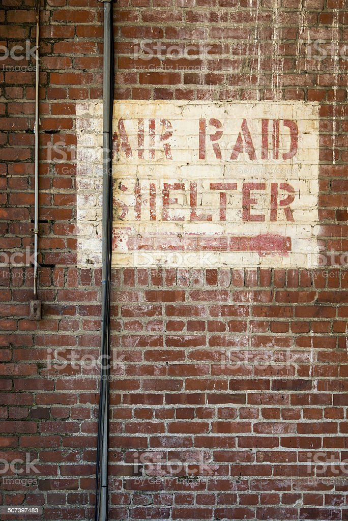 Air Raid Shelter Sign Painted on a Brick Warehouse stock photo