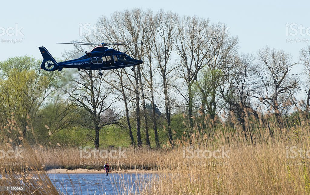 air rescue helicopter with a man on the rope stock photo