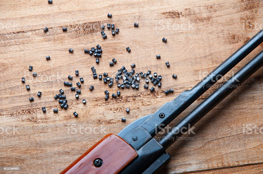 Air rifle and pellet on a wooden background stock photo