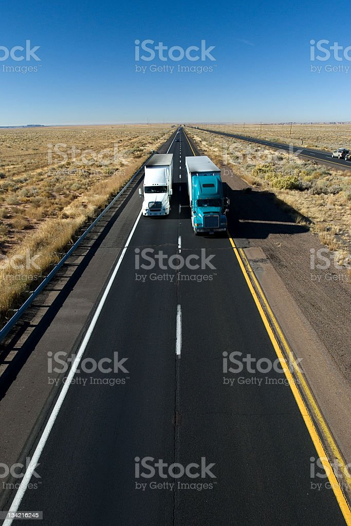 Air shot of two trucks moving across a long road stock photo