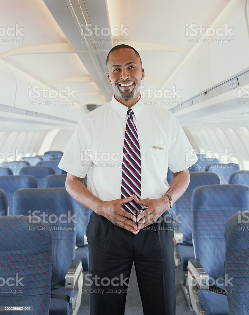 Air steward standing in aisle of aeroplane, smiling, portrait stock photo