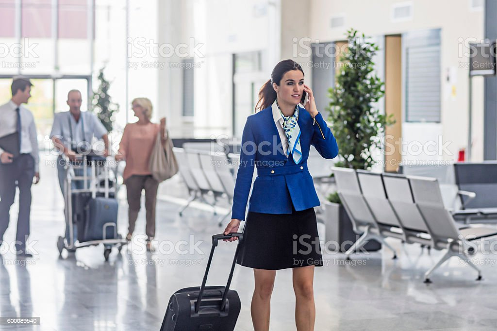 Air stewardess pulling luggage while answering mobile phone in airport stock photo