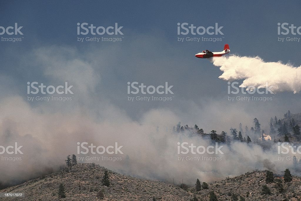 Air tanker spraying water on hillside fire. stock photo
