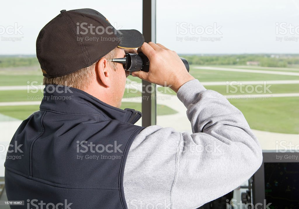 Air Traffic Controller Looking Out at Runway with Binoculars stock photo