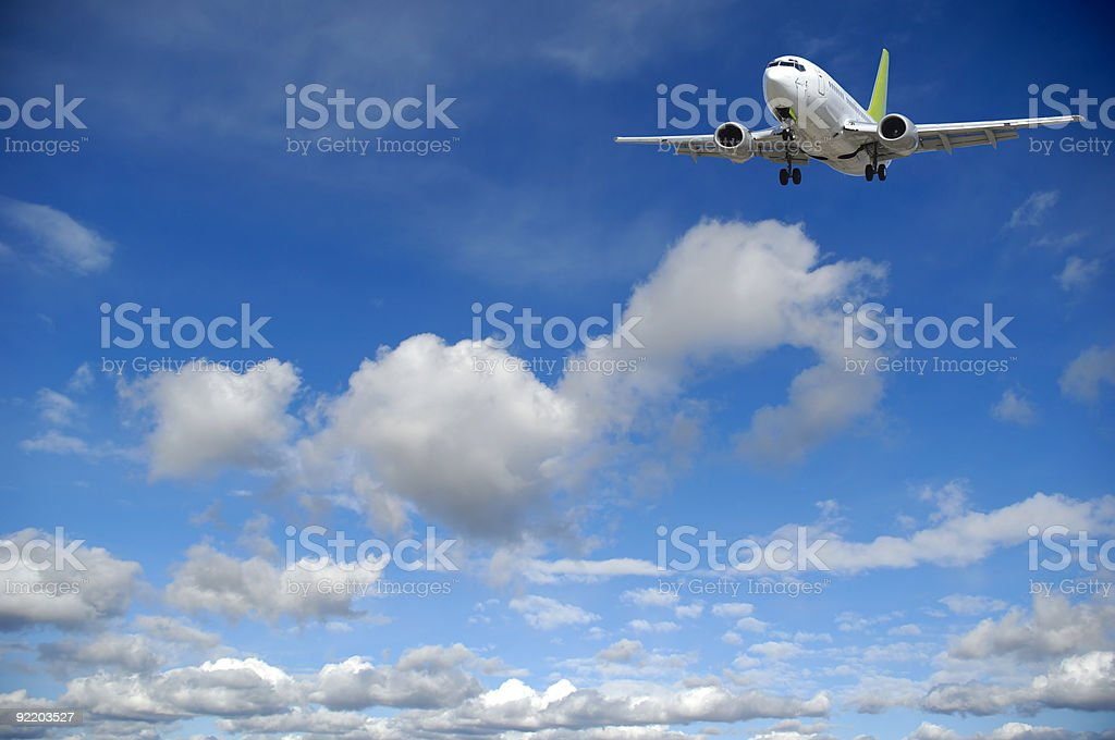 Air travel - Plane flying in blue sky with clouds royalty-free stock photo