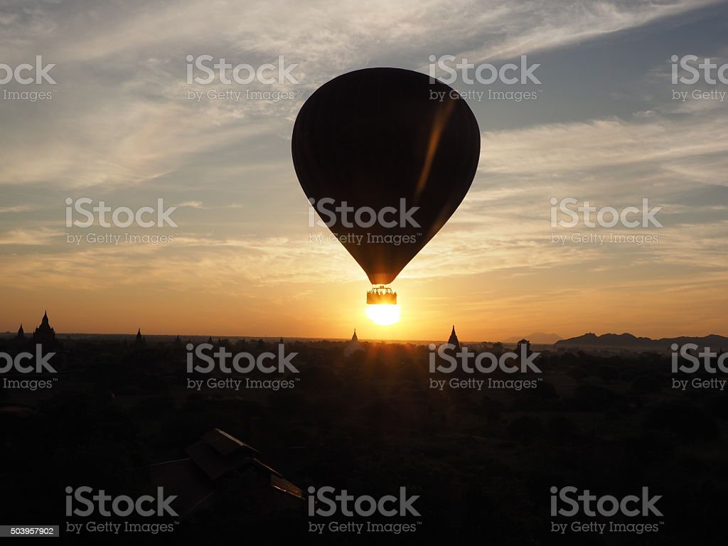 Airballoon over the sun during sunrise stock photo